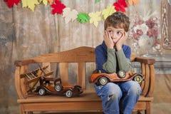 Menino que joga com os carros de madeira do brinquedo Imagem de Stock