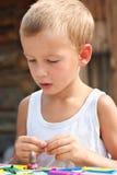 Menino que joga com plasticine. Imagem de Stock