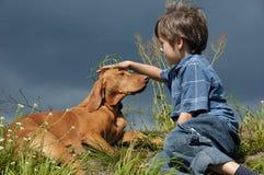 Menino que joga com seu cão Fotografia de Stock Royalty Free