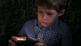Menino que joga com telefone video estoque