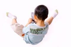 Menino que joga com telemóvel Fotografia de Stock Royalty Free