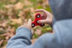 Menino que joga com um girador vermelho da inquietação Foto de Stock