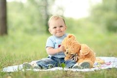 Menino que joga com um urso de peluche na grama Imagem de Stock