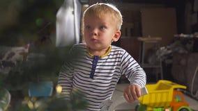 Menino que joga com uma bicicleta doada perto da árvore de Natal vídeos de arquivo