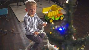 Menino que joga com uma bicicleta doada perto da árvore de Natal filme