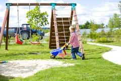 Menino que joga em um campo de jogos com areia Fotos de Stock Royalty Free