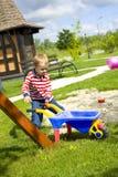 Menino que joga em um campo de jogos com areia Imagens de Stock Royalty Free