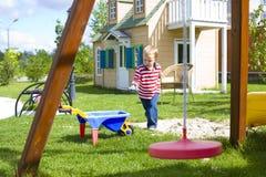 Menino que joga em um campo de jogos com a areia exterior Fotografia de Stock