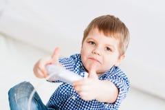 Menino que joga em um console do jogo Fotos de Stock