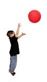 Menino que joga a esfera vermelha sobre o branco Imagens de Stock Royalty Free