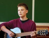 Menino que joga a guitarra foto de stock