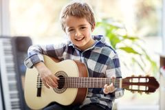 Menino que joga a guitarra acústica foto de stock