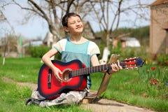 Menino que joga a guitarra ao ar livre Fotos de Stock Royalty Free