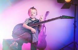 Menino que joga a guitarra, guitarrista da criança foto de stock