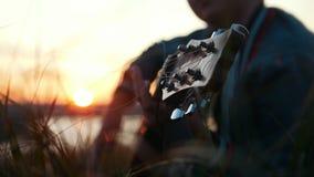 Menino que joga a guitarra no campo no por do sol no fundo brilhante do céu vídeos de arquivo