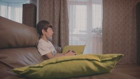 Menino que joga jogos de vídeo no console sobre o sofá em casa vídeos de arquivo