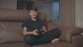 Menino que joga jogos de vídeo no console sobre o sofá em casa video estoque
