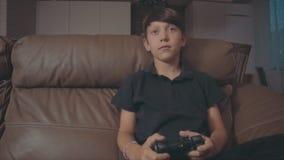 Menino que joga jogos de vídeo no console sobre o sofá em casa filme