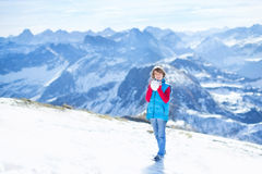 Menino que joga a luta da bola da neve em montanhas da neve Imagem de Stock Royalty Free