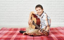 Menino que joga a música na guitarra, sentando-se em uma cobertura quadriculado vermelha, fundo branco da parede de tijolo foto de stock