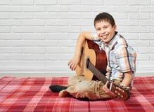 Menino que joga a música na guitarra, sentando-se em uma cobertura quadriculado vermelha, fundo branco da parede de tijolo foto de stock royalty free