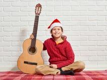 Menino que joga a música na guitarra, vestida em uma camiseta e em um chapéu de lã vermelhos de Santa, sentando-se em uma cobertu imagens de stock royalty free