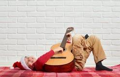 Menino que joga a música na guitarra, vestida em uma camiseta e em um chapéu de lã vermelhos de Santa, sentando-se em uma cobertu foto de stock