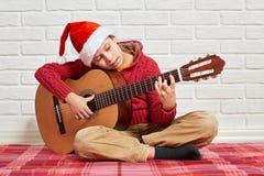 Menino que joga a música na guitarra, vestida em uma camiseta e em um chapéu de lã vermelhos de Santa, sentando-se em uma cobertu imagem de stock royalty free