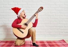 Menino que joga a música na guitarra, vestida em uma camiseta e em um chapéu de lã vermelhos de Santa, sentando-se em uma cobertu fotos de stock royalty free