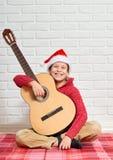 Menino que joga a música na guitarra, vestida em uma camiseta e em um chapéu de lã vermelhos de Santa, sentando-se em uma cobertu fotografia de stock royalty free