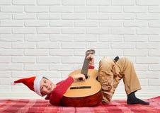 Menino que joga a música na guitarra, vestida em uma camiseta e em um chapéu de lã vermelhos de Santa, sentando-se em uma cobertu fotografia de stock