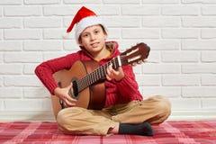 Menino que joga a música na guitarra, vestida em uma camiseta e em um chapéu de lã vermelhos de Santa, sentando-se em uma cobertu imagem de stock