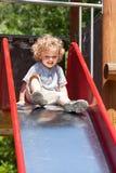 Menino que joga na corrediça Foto de Stock Royalty Free