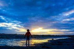 Menino que joga na praia no por do sol Foto de Stock
