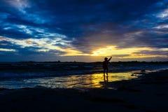 Menino que joga na praia no por do sol Imagem de Stock Royalty Free