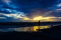 Menino que joga na praia no por do sol Imagens de Stock Royalty Free