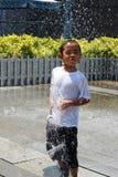 Menino que joga no chuveiro de Sun imagens de stock royalty free