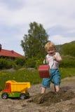 Menino que joga no sandpit Fotografia de Stock