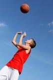Menino que joga o basquetebol com esfera Fotografia de Stock Royalty Free