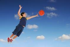 Menino que joga o basquetebol que salta e que voa fotos de stock