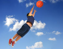 Menino que joga o basquetebol. Voo com céu azul Fotografia de Stock