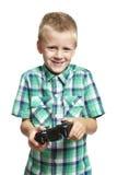 Menino que joga o console dos jogos Fotografia de Stock