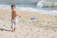 Menino que joga o frisbee na praia Fotografia de Stock Royalty Free