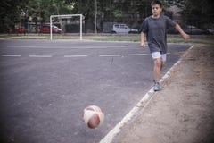 Menino que joga o futebol Imagens de Stock