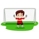 Menino que joga o futebol como o goleiros Fotografia de Stock