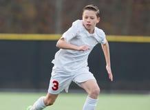 Menino que joga o futebol no jogo Fotografia de Stock