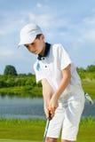 Menino que joga o golfe Imagens de Stock