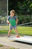 Menino que joga o mini golfe Fotografia de Stock