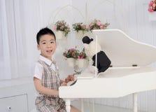 Menino que joga o piano Fotos de Stock Royalty Free