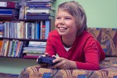 Menino que joga um console do jogo de vídeo Foto de Stock Royalty Free